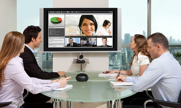 Group of business people having a video conference meeting. Sitting around a conference table talking and networking.