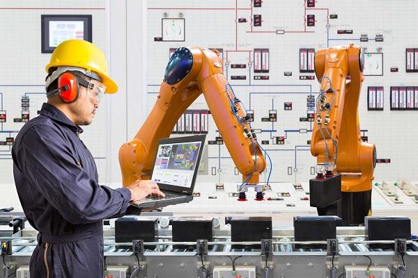 A Senior Industrial Person Operating Collaborative Robot Through His Laptop.